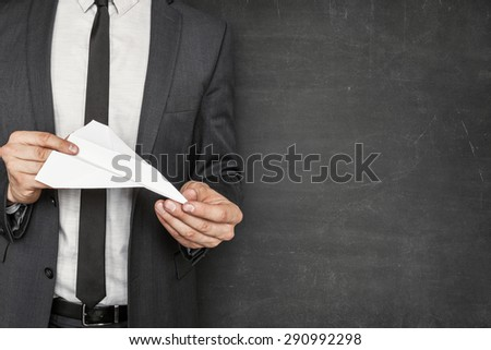 Empty blackboard with businessman on side holding paper plane in hands