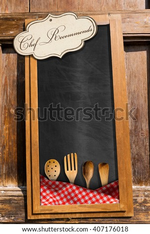 Empty blackboard with checkered tablecloth, kitchen utensils and label with text Chef Recommends. Template for a restaurant menu - stock photo