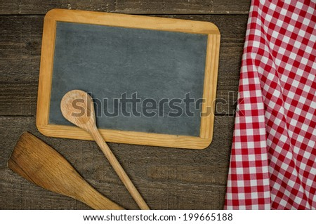 Empty blackboard with wooden spoons and red checkered tablecloth - stock photo