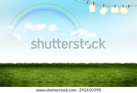 empty blank cards hanging with clips over colorful rainbow green grass lawn field and white clouds blue sky background. Hope, happy, nature, natural idea template background - stock photo