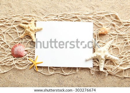 Empty blank of sheet paper on beach sand with sea shells - stock photo