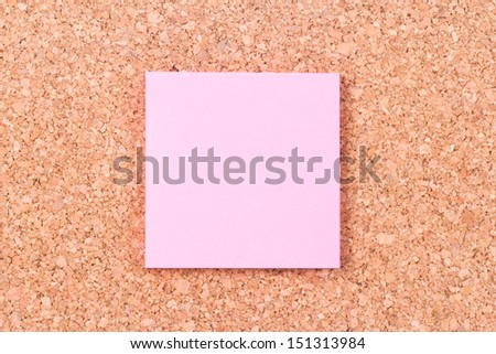 Empty, blank, pink sticky post it note paper on cork plate.