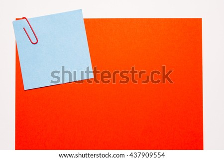 Empty blue and red notepaper with blue paper clip - stock photo