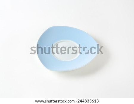 empty blue and white saucer on white background