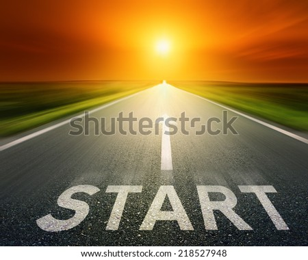 Empty blurred asphalt road towards the setting sun. Concept with arrow and sign start - stock photo