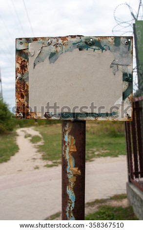 Empty board on a metallic pole by the meadow path - stock photo