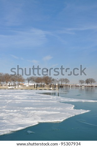 Empty Boat Harbor on Lake Michigan filled with Snow and Ice on north side of Chicago Illinois on sunny blue sky winter day - stock photo