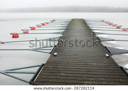 empty boat park on the lake in winter under the snow - stock photo