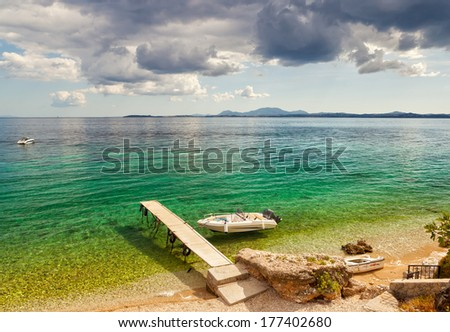 Empty boat standing at wooden pier under bright sunlight and heavy clouds with shadow on pebbles at sea floor seen through transparent water near Ipsos beach, Corfu, Greece - stock photo