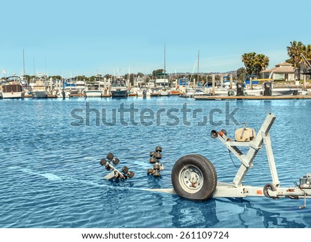 Empty boat trailer in water at the harbor. Used to transport small boats in and out of the water. View of yachts docked in marina in background. - stock photo
