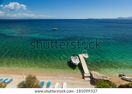 Empty boats standing at wooden pier under bright sunlight with shadow on pebbles at sea floor seen through transparent water of Ionian sea, Corfu, Greece