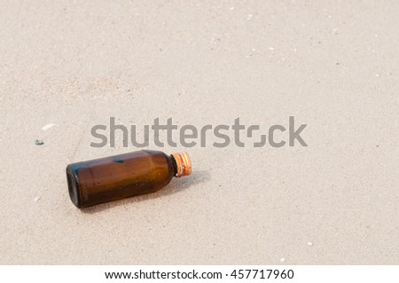 Empty bottle on the beach. - stock photo