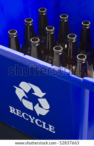 Empty bottles in blue recycle bin - stock photo