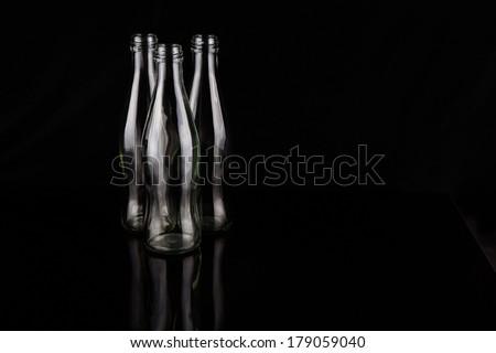 Empty bottles over black background - stock photo