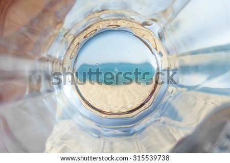 Empty bottom mug of drained fresh beer on the beach - stock photo