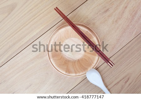 Empty bowl, spoon and chopsticks wooden on wood table background