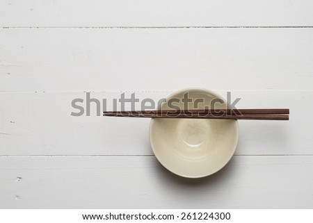 empty bowl with chop sticks on wooden white table - stock photo