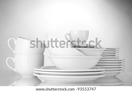 empty bowls, plates and cups on gray background - stock photo