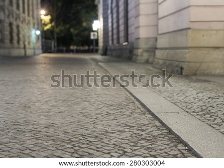 empty brick road at night with blurred background, historic midtown of Berlin, Germany, Europe