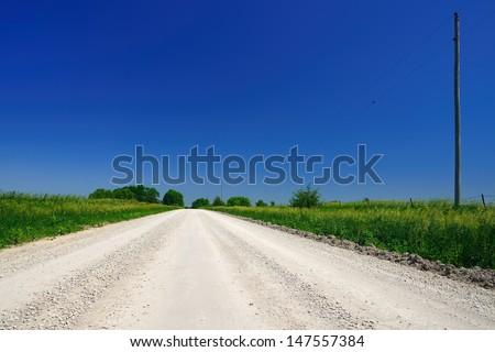 Empty bright gravel dirt road heading into distance under deep blue sky - stock photo