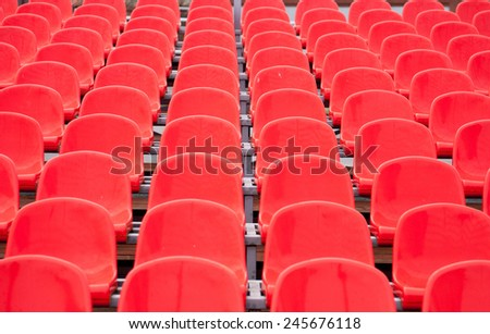 Empty bright red plastic seats in a stadium. - stock photo