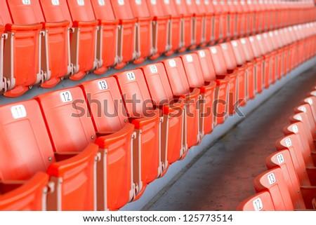 Empty bright red stadium seats - stock photo