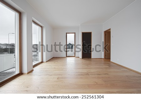 empty bright room with three windows and wooden flore - stock photo