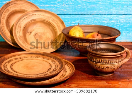 Empty brown clay plates bowls mug with ornament pattern on a blue wooden background & Empty Brown Clay Plates Bowls Mug Stock Photo (Royalty Free ...