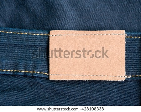 Empty brown leather tag with jean and seam in background. Highly detailed closeup of blank leather label tag on blue jeans. - stock photo