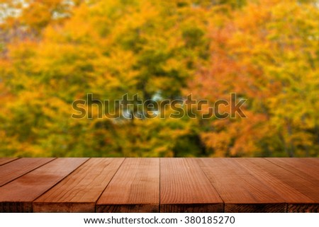 Empty brown wooden table and blurred abstract background of Beautiful Colorful Autumn Leaves with bokeh image, for product display montage,can be used for montage or display your products - stock photo