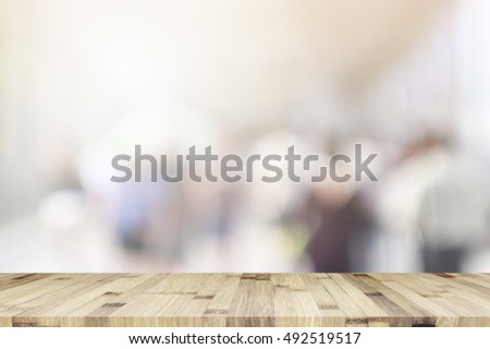 empty brown wooden table and Coffee shop blur background with bokeh image, for product display montage