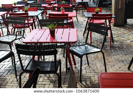 Empty cafe with grey and red tables and chairs after a rain shower, Amsterdam