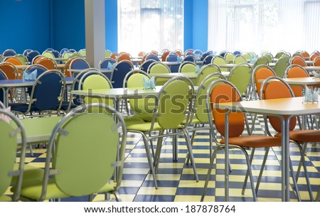 Empty cafeteria with blue, green, orange chairs - stock photo