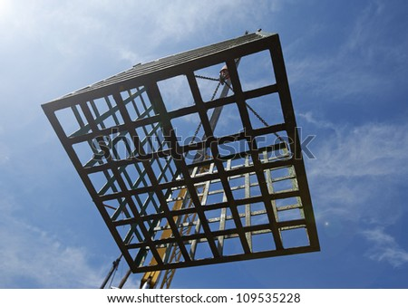 Empty cage moving down against blue sky - stock photo
