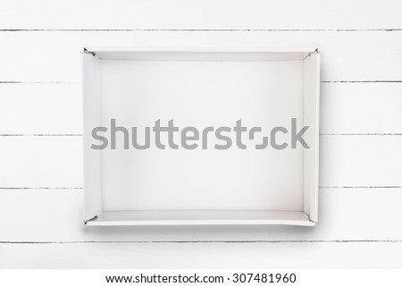 Empty cardboard box on white wooden background - stock photo
