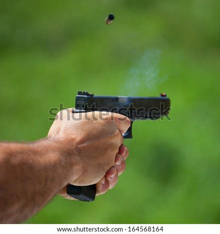 Empty cartridge just above a polymer handgun that has been shot - stock photo
