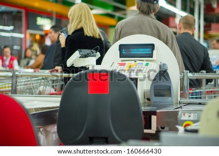 Empty cash desk and queue of customers on back in supermarket - stock photo