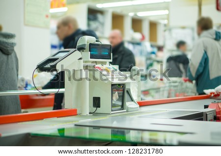 Empty cash desk with payment terminal and customers in queue in supermarket - stock photo