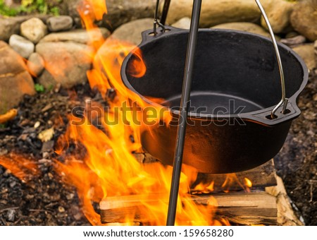Empty cauldron on the fire ready for cooking - stock photo