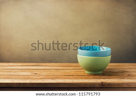 Empty ceramic bowls on wooden table against grunge wall