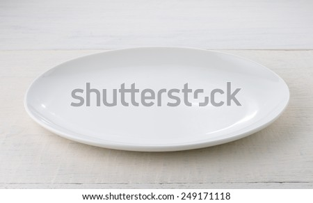 Empty ceramic plate on wooden table - stock photo