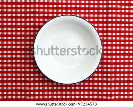 Empty cereal bowl isolated on red and white checkered background - stock photo