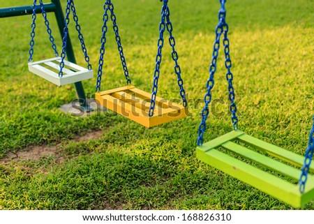 Empty chain swings in children playground - stock photo