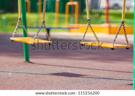 Empty chain swings on summer kids playground - stock photo