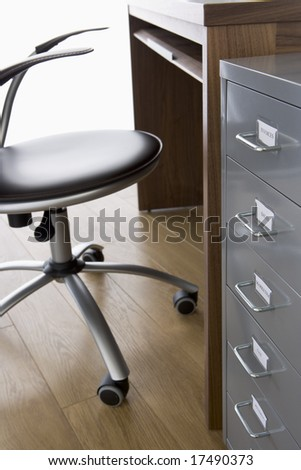 Empty Chair And Desk With Filing Cabinet - stock photo