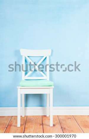 Empty chair on blue wall in interieur - stock photo