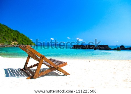 Empty chair on the beautiful beach under the clear blue sky at Koh Mak in Thailand - stock photo