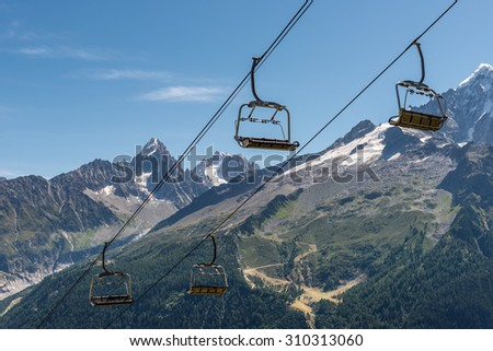 Empty chairlift  in French Alps in summer . Mountains background.