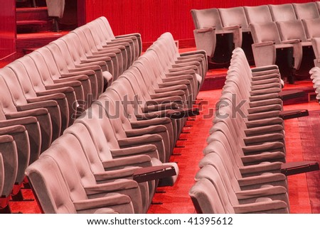 Empty chairs at cinema or theater, red tone - stock photo
