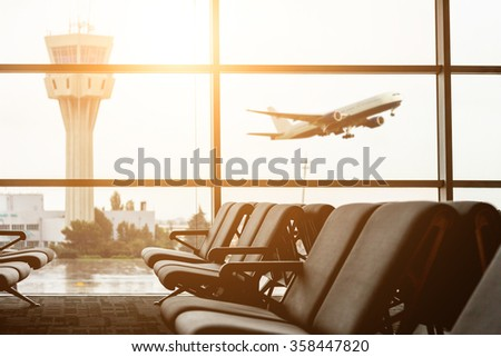 Empty chairs in the departure hall at airport , with the control tower and an airplane taking off at sunset. Travel and transportation concepts. - stock photo